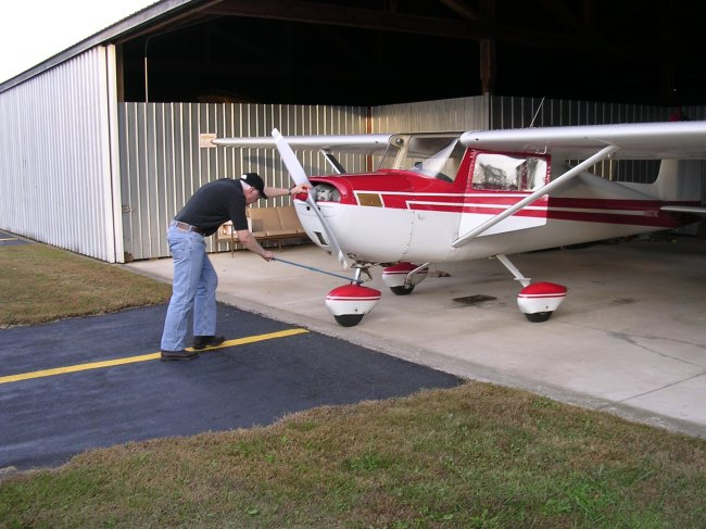 Dad putting the plane away in the hangar after flying
